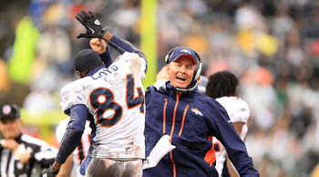 OAKLAND, CA - DECEMBER 19:  Offensive Coordinator Mike McCoy celebrates with Brandon Lloyd #84 of the Denver Broncos after they scored a touchdown against the Oakland Raiders at Oakland-Alameda County Coliseum on December 19, 2010 in Oakland, California.