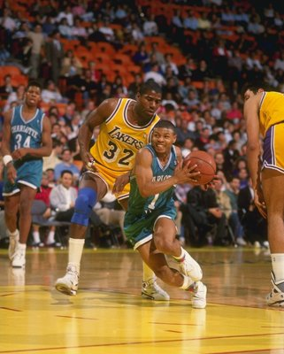 1990-1991:  Guard Tyrone (Muggsy) Bogues of the Charlotte Hornets (center) keeps the ball away from guard Magic Johnson of the Los Angeles Lakers (left) during a game at the Great Western Forum in Inglewood, California. Mandatory Credit: Ken Levine  /Alls