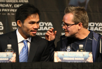 LAS VEGAS - DECEMBER 3:  Boxer Manny Pacquiao (L) of the Philippines speaks with his trainer Freddie Roach at the final press conference at the MGM Grand Garden Arena December 3, 2008 in Las Vegas, Nevada. Boxer Oscar de la Hoya fights Manny Pacquiao Dece