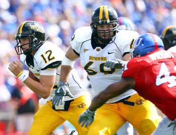 LAWRENCE, KS - SEPTEMBER 26:  Quarterback Austin Davis #12 of the Southern Mississippi Golden Eagles scrambles as Micah Brown #69 throws a block during the game against the Kansas Jayhawks on September 26, 2009 at Memorial Stadium in Lawrence, Kansas.  (P