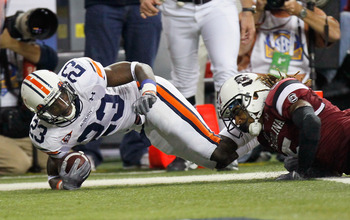 ATLANTA, GA - DECEMBER 04:  Onterio McCalebb #23 of the Auburn Tigers dives for a touchdown against Stephon Gilmore #5 of the South Carolina Gamecocks during the 2010 SEC Championship at Georgia Dome on December 4, 2010 in Atlanta, Georgia.  (Photo by Kev