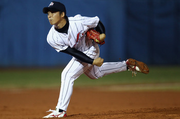 GUANGZHOU, CHINA - NOVEMBER 15: Manabu Mima of Japan pitches during the Men's Preliminary match between Japan and China at Aoti Baseball Field 1 during day three of the 16th Asian Games Guangzhou 2010 on November 15, 2010 in Guangzhou, China.  (Photo by H