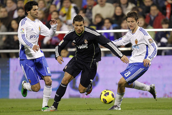 ZARAGOZA, SPAIN - DECEMBER 12: Cristiano Ronaldo of Real Madrid beats Ander Herrera and Angel Lafita of Zaragoza during the La Liga match between Real Zaragoza and Real Madrid at La Romareda stadium on December 12, 2010 in Zaragoza, Spain. (Photo by Angel