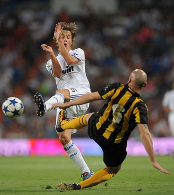 MADRID, SPAIN - AUGUST 24: Sergio Canales (L) of Real Madrid is tackled by Guillermo Rodriguez of Penarol during the Santiago Bernabeu Trophy match between Real Madrid and Penarol at the Santiago Bernabeu stadium on August 24, 2010 in Madrid, Spain.  (Pho
