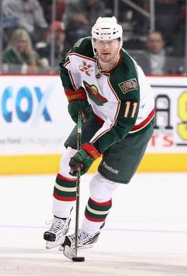 GLENDALE, AZ - DECEMBER 09:  John Madden #11 of the Minnesota Wild skates with the puck during the NHL game against the Phoenix Coyotes at Jobing.com Arena on December 9, 2010 in Glendale, Arizona.  The Wild defeated the Coyotes 3-2.  (Photo by Christian