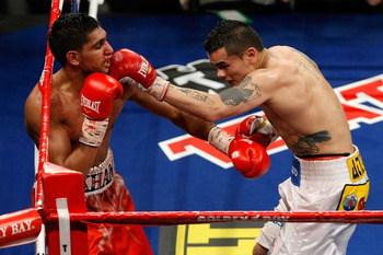 LAS VEGAS - DECEMBER 11:  (R-L) Marcos Maidana of Argentina connects with a left at Amir Khan of England during the WBA super lightweight title fight at Mandalay Bay Events Center on December 11, 2010 in Las Vegas, Nevada.  (Photo by Ethan Miller/Getty Im