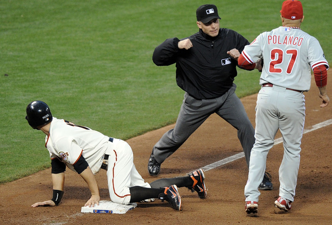 SAN FRANCISCO - OCTOBER 21:  Umpire Dan Iassogna calls out Cody Ross #13 of the San Francisco Giants as he is tagged by Placido Polanco #27 of the Philadelphia Phillies in the fourth inning in Game Five of the NLCS during the 2010 MLB Playoffs at AT&T Par