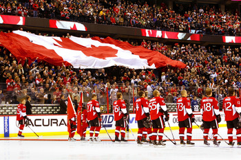 OTTAWA, CANADA - NOVEMBER 11:  The Ottawa Senators stand at the blue line as the Canadian flag passes through the crowd prior to a game against the Vancouver Canucks on Remembrance Day at Scotiabank Place on November 11, 2010 in Ottawa, Ontario, Canada.
