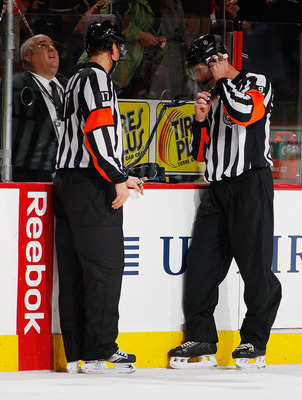 PHILADELPHIA - DECEMBER 08:  Referee Dan O'Rourke #9 reviews Mike Richards #18 (not shown) of the Philadelphia Flyers overtime goal after a replay showed time expired an instant before the puck crossed the line and was waved off against the San Jose Shark