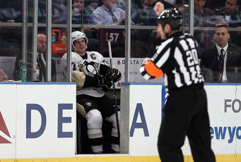NEW YORK - MARCH 04:  Sidney Crosby #87 of the Pittsburgh Penguins sits in the penalty box against the New York Rangers after referee Tim Peel makes a holding call on March 4, 2010 at Madison Square Garden in New York City.  (Photo by Jim McIsaac/Getty Im
