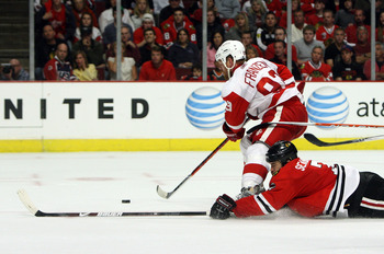 CHICAGO - MAY 24:  Johan Franzen #93 of the Detroit Red Wings skates with the puck as Brent Seabrook #7 the Chicago Blackhawks slides head first down the ice behind him during Game Four of the Western Conference Championship Round of the 2009 Stanley Cup