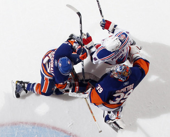 UNIONDALE, NY - DECEMBER 02:  Rick DiPietro #39  and Andrew MacDonald #47 of the New York Islanders defend against Brandon Prust #8 of the New York Rangers at the Nassau Coliseum on December 2, 2010 in Uniondale, New York.  (Photo by Bruce Bennett/Getty I