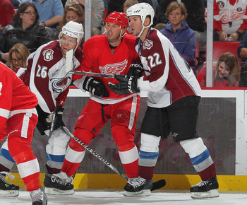 DETROIT,MI - NOVEMBER 13:  Mike Modano #90 of the Detroit Red Wings is sandwiched by Paul Stastny #26 and Scott Hannan #22 of the Colorado Avalanche in a game on November 13,2010 at the Joe Louis Arena in Detroit, Michigan. The Wings defeated the Avalanch