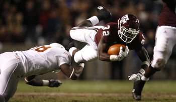 COLLEGE STATION, TX - NOVEMBER 26: Tailback Cyrus Gray #32 of the Texas A&M Aggies is tripped up by a Texas Longhorns defender in the second half at Kyle Field on November 26, 2009 in College Station, Texas. The Longhorns defeated the Aggies 49-39. (Photo