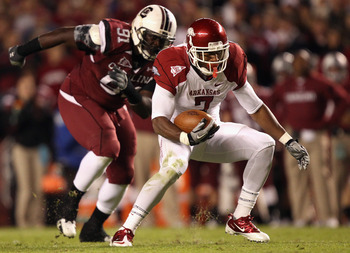 COLUMBIA, SC - NOVEMBER 06:  Knile Davis #7 of the Arkansas Razorbacks runs with the ball as Ladi Ajiboye #91 of the South Carolina Gamecocks runs after him during their game at Williams-Brice Stadium on November 6, 2010 in Columbia, South Carolina.  (Pho