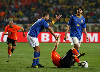 PORT ELIZABETH, SOUTH AFRICA - JULY 02:  Felipe Melo of Brazil attempts to pull up to his feet the injured Arjen Robben of the Netherlands, Melo receives a red card and is sent off for the challenge during the 2010 FIFA World Cup South Africa Quarter Fina
