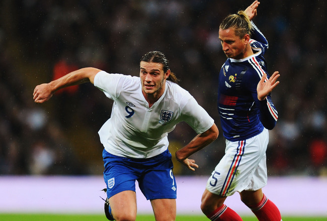 LONDON, ENGLAND - NOVEMBER 17:  Andy Carroll (L) of England holds off the challenge of Philippe Mexes (R) of France during the international friendly match between England and France at Wembley Stadium on November 17, 2010 in London, England.  (Photo by M