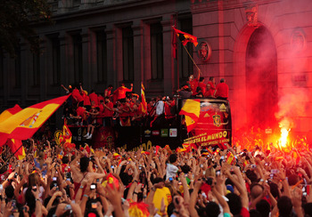 MADRID, SPAIN - JULY 12:  Crowds cheer for the Spanish team as they travel in an open bus as part of the FIFA 2010 World Cup victory parade in Plaza Cibeles on July 12, 2010 in Madrid, Spain.  (Photo by Denis Doyle/Getty Images)