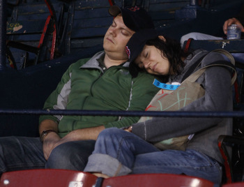 BOSTON - AUGUST 24:  Fans take a nap as they wait for an announcement about the game between the Seattle Mariners and the Boston Red Sox on August 24, 2010 at Fenway Park in Boston, Massachusetts. Tonight's game has been postponed and the teams will play