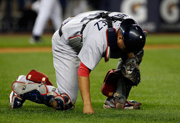 NEW YORK - SEPTEMBER 26:  Victor Martinez #41 of the Boston Red Sox kneels in pain after throwing the ball away for an error on Brett Gardner (not shown) of the New York Yankees bunt attempt in the 10th inning on September 26, 2010 at Yankee Stadium in th