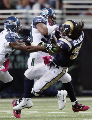 ST. LOUIS - OCTOBER 03:  Raheem Brock #98 and Lawyer Milloy #36 of the Seattle Seahawks take down Steven Jackson #39 of the St. Louis Rams on October 3, 2010 at Edward Jones Dome in St. Louis, Missouri.  (Photo by Elsa/Getty Images)