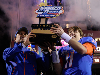 LAS VEGAS, NV - DECEMBER 22:  Head coach Chris Petersen (L) and quarterback Kellen Moore #11 of the Boise State Broncos hold up a trophy as they celebrate their 26-3 victory over the Utah Utes in the MAACO Bowl Las Vegas at Sam Boyd Stadium December 22, 2