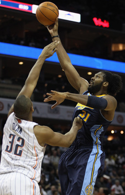 CHARLOTTE, NC - DECEMBER 07:  Nene #31 of the Denver Nuggets shoots the ball over Boris Diaw #32 of the Charlotte Bobcats during their game at Time Warner Cable Arena on December 7, 2010 in Charlotte, North Carolina.  NOTE TO USER: User expressly acknowle