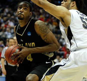 MILWAUKEE - MARCH 19:  Keith Benson #34 of the Oakland Golden Grizzlies looks to shoot over Gary McGhee #52 of the of the Pittsburgh Panthers in the first half during the first round of the 2010 NCAA men's basketball tournament at the Bradley Center on Ma