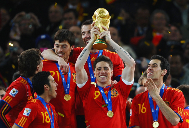 JOHANNESBURG, SOUTH AFRICA - JULY 11:  Fernando Torres of Spain lifts the World Cup trophy as the Spain team celebrate victory following the 2010 FIFA World Cup South Africa Final match between Netherlands and Spain at Soccer City Stadium on July 11, 2010