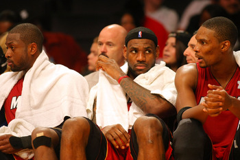LOS ANGELES, CA - DECEMBER 25:  (L-R) Dwyane Wade #3, LeBron James #6 and Chris Bosh #11 of the Miami Heat look on from the bench area during the NBA game against the Los Angeles Lakers at Staples Center on December 25, 2010 in Los Angeles, California. Th