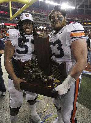 ATLANTA - DECEMBER 4:  Lineman Bryon Isom #57 (left) and Bart Eddins #53 of the Auburn Tigers celebrate with the SEC Championship trophy after the 2010 SEC Championship against the South Carolina Gamecocks at Georgia Dome on December 4, 2010 in Atlanta, G