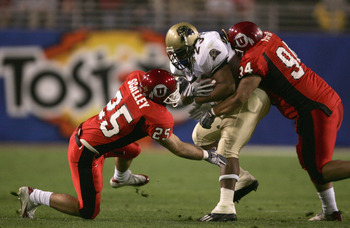 TEMPE, AZ - JANUARY 1:  Tim Murphy #23 of Pittsburgh is stopped by Steve Fifita #94 (R) and Morgan Scalley #25 (L) of Utah during the Tostito's Fiesta Bowl at the Sun Devil Stadium on January 1, 2005 in Tempe, Arizona.  Utah won the game with the score of