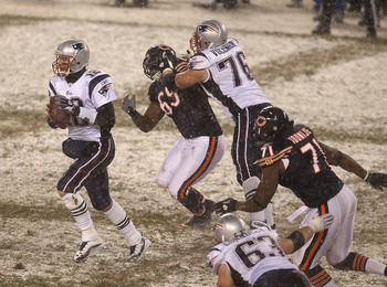 CHICAGO, IL - DECEMBER 12: Tom Brady #12 of the New England Patriots looks for a receiver as teammate Sebastian Vollmer #76 blocks Henry Melton #69 of the Chicago Bears and Israel Idonije #71 rushes at Soldier Field on December 12, 2010 in Chicago, Illino