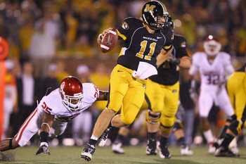 COLUMBIA, MISSOURI - OCTOBER 23: Blaine Gabbert #11 of the Missouri Tigers looks to get away from Emmanuel Jones #25 of the Oklahoma Sooners at Faurot Field/Memorial Stadium on October 23, 2010 in Columbia, Missouri.  The Tigers beat the Sooners 36-27.  (