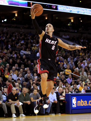 OAKLAND, CA - DECEMBER 10:  Carlos Arroyo #8 of the Miami Heat goes up for a layup against the Golden State Warriors at Oracle Arena on December 10, 2010 in Oakland, California. NOTE TO USER: User expressly acknowledges and agrees that, by downloading and