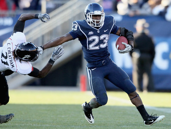 EAST HARTFORD, CT - NOVEMBER 27:  Jordan Todman #23 of the Connecticut Huskies carries the ball as Camerron Cheatham #21 of the Cincinnati Bearcats defends on November 27, 2010 at Rentschler Field in East Hartford, Connecticut. The Huskies defeated the Be