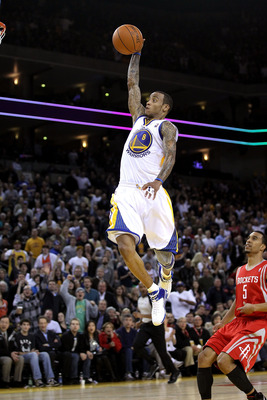 OAKLAND, CA - DECEMBER 20:  Monta Ellis #8 of the Golden State Warriors dunks the ball over Courtney Lee #5 of the Houston Rockets at Oracle Arena on December 20, 2010 in Oakland, California. NOTE TO USER: User expressly acknowledges and agrees that, by d