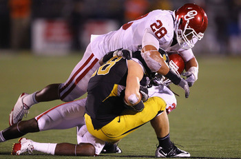 COLUMBIA, MISSOURI - OCTOBER 23: T.J. Moe #28 of the Missouri Tigers is tackled by Travis Lewis #28 of the Oklahoma Sooners at Faurot Field/Memorial Stadium on October 23, 2010 in Columbia, Missouri.  The Tigers beat the Sooners 36-27.  (Photo by Dilip Vi