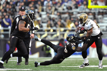 BALTIMORE, MD - DECEMBER 19:  Reggie Bush #25 of the New Orleans Saints is tackled by Tavares Gooden #56 of the Baltimore Ravens  at M&T Bank Stadium on December 19, 2010 in Baltimore, Maryland. The Ravens defeated the Saints 30-24. (Photo by Larry French