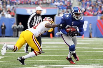 EAST RUTHERFORD, NJ - DECEMBER 05:  Derek Hagan #85 of the New York Giants eludes a tackle from Phillip Buchanon #31 of the Washington Redskins on December 5, 2010 at the New Meadowlands Stadium in East Rutherford, New Jersey.  (Photo by Jim McIsaac/Getty