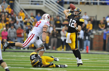IOWA CITY, IA - OCTOBER 23- Quarterback Ricky Stanzi #12 of the University of Iowa Hawkeyes throws under pressure from defensive lineman J.J. Watt #99 of the Wisconsin Badgers during the second half of play at Kinnick Stadium on October 23, 2010 in Iowa C