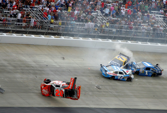 DOVER, DE - SEPTEMBER 27:  (L-R) Joey Logano, driver of the #20 Home Depot Toyota, flips his car after he was involved in a wreck with Reed Sorenson, driver of the #43 Valvoline Dodge, Robby Gordon, driver of the #7 Camping World Toyota and Martin Truex J