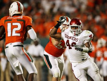 MIAMI GARDENS, FL - OCTOBER 03:  Quarterback Jacory Harris #12 of the Miami Hurricanes drops back to pass as defensive end Jeremy Beal #44 of the Oklahoma Sooners gets past offensive lineman Matt Pipho #65 at Land Shark Stadium on October 3, 2009 in Miami