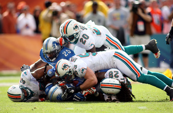 MIAMI - DECEMBER 26: Stefan Logan #11 of the Detroit Lions is gang tackled by the Miami Dolphins at Sun Life Stadium on December 26, 2010 in Miami, Florida.  (Photo by Marc Serota/Getty Images)