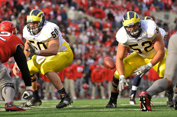 COLUMBUS, OH - NOVEMBER 27:  David Molk #50 of the Michigan Wolverines and Stephen Schilling #52 of the Michigan Wolverines block against the Ohio State Buckeyes at Ohio Stadium on November 27, 2010 in Columbus, Ohio.  (Photo by Jamie Sabau/Getty Images)