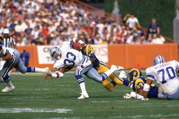 ANAHEIM, CA - JANUARY 4:  Running back Tony Dorsett #33 of the Dallas Cowboys gets tackled by defensive back Johnnie Johnson #20 of the Los Angeles Rams during a 1985 NFC Divisional Playoff game at Anaheim Stadium on January 4, 1996 in Anaheim, California
