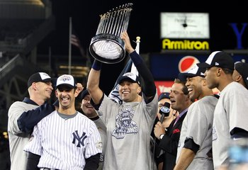 NEW YORK - NOVEMBER 04:  Derek Jeter #2 of the New York Yankees holds up the trophy as he celebrates with A.J. Burnett (L), Jorge Posada (2nd L), Mariano Rivera (2nd R) and Robinson Cano after their 7-3 win against the Philadelphia Phillies in Game Six of