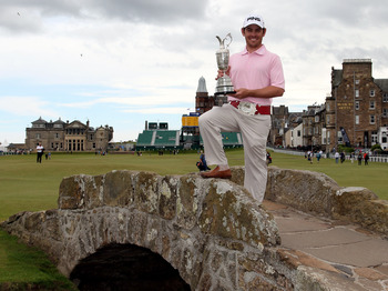 ST ANDREWS, SCOTLAND - JULY 19:  Open Champion Louis Oosthuizen of South Africa poses with the Claret Jug on the Swilken bridge on July 19, 2010 in St Andrews, Scotland  (Photo by Ross Kinnaird/Getty Images)