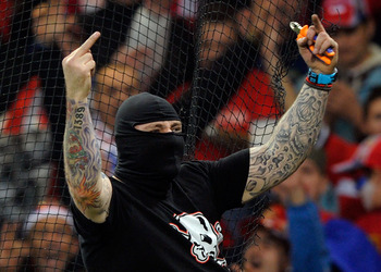 GENOA, ITALY - OCTOBER 12:  Balaclava clad Serbian fan Ivan Bogdanov gestures towards riot police during the UEFA Euro 2012 qualifying match between Italy and Serbia at Luigi Ferraris Stadium on October 12, 2010 in Genoa, Italy.  (Photo by Claudio Villa/G