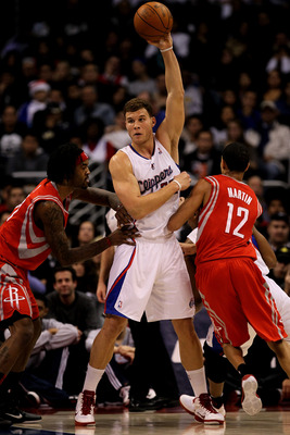 LOS ANGELES, CA - DECEMBER 22:   Blake Griffin #32 of the Los Angeles Clippers grabs a pass over Kevin Martin #12 and Jordan Hill #27 of the Houston Rockets at Staples Center on December 22, 2010 in Los Angeles, California.  NOTE TO USER: User expressly a